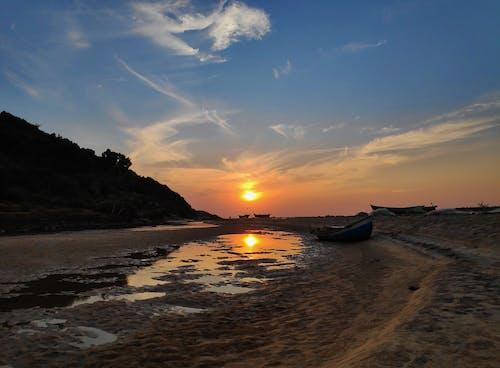 Photo of Boats on Seashore During Sunset
