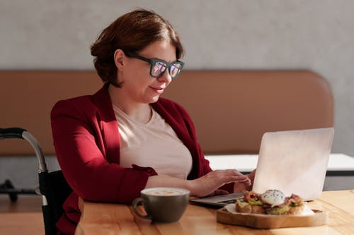 Photo of Woman Wearing Eyeglasses While Using Laptop