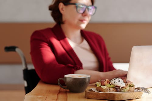 Woman in Red Blazer Wearing Black Framed Eyeglasses Sitting at the Table