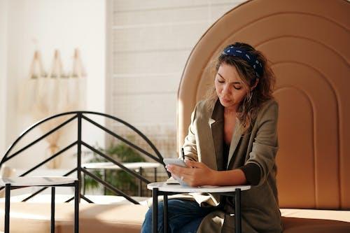 Woman in Brown Blazer Sitting on Chair