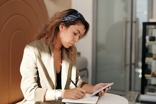 Woman Holding Smartphone Writing on Notebook