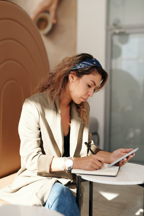 Woman Busy Writing on Her Notebook