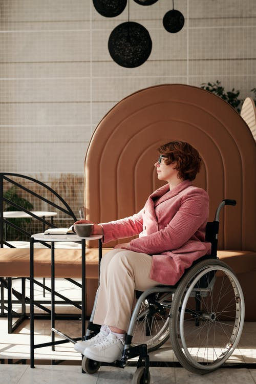 Woman in Pink Sweater Sitting on Black Wheelchair