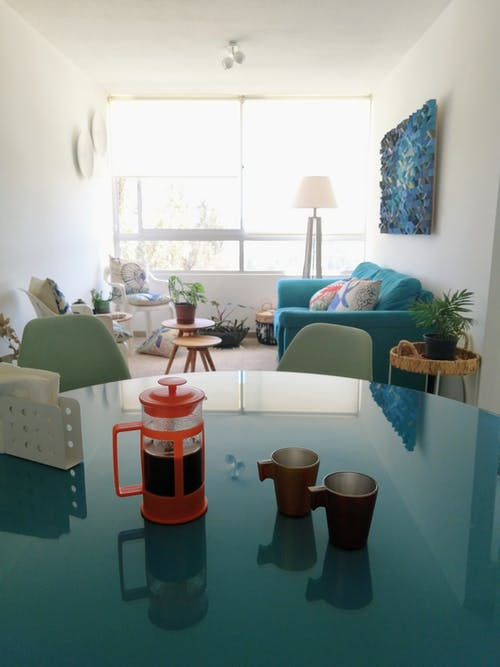 Glass table with cups and tea placed in cozy living room near couch