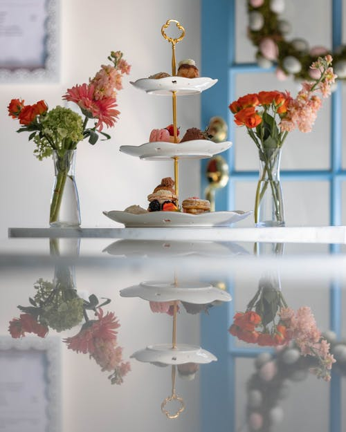 Vases of fresh flowers and ceramic plates of delicious desserts placed on white table