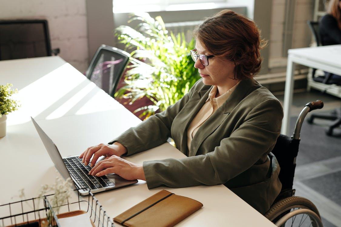 Woman in Brown Jacket Using Macbook Pro