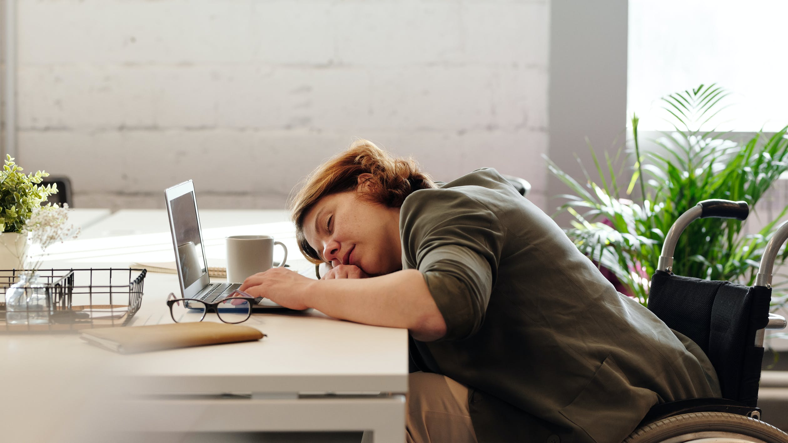 A woman laying her head down on a table in front of her open laptop. Photo used courtesy of Pexels.com