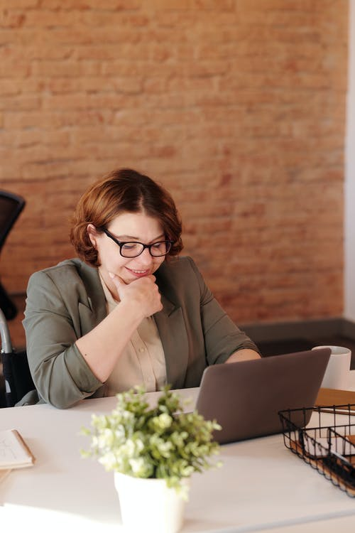 Photo of Woman Smiling While Using Laptop
