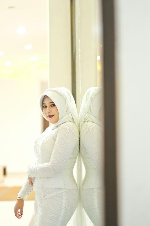 Woman in White Knit Sweater Standing Near Window
