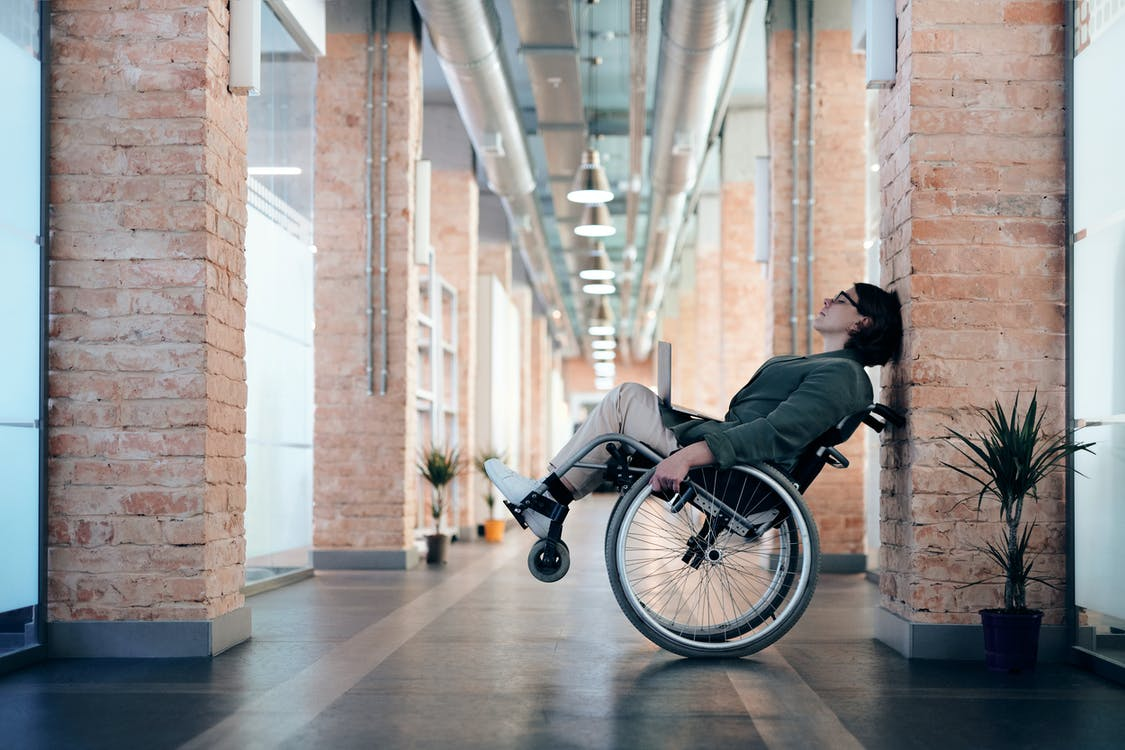 Photo of Woman Sitting on Wheelchair While Leaning on Wall
