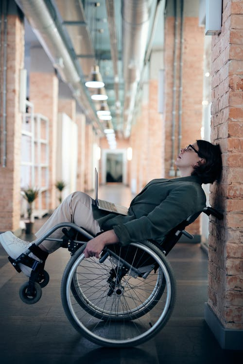Woman Sitting on Wheelchair While Leaning on Wall