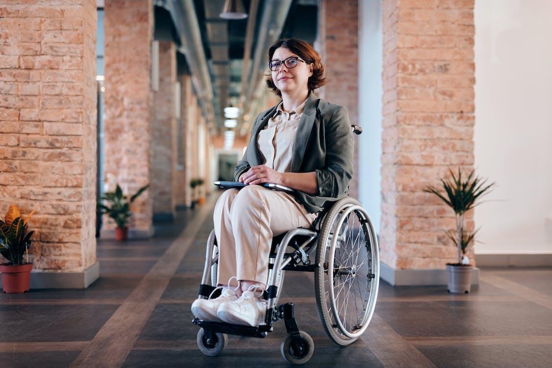 Woman in Gray Coat Sitting on Black Wheelchair