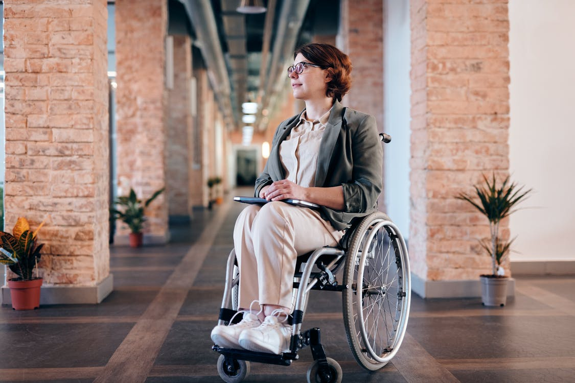 Woman in Gray Coat Sitting on Wheelchair