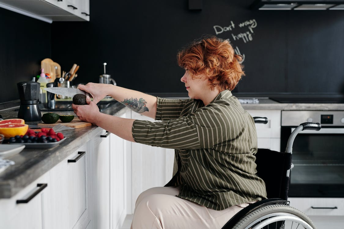 Photo of Woman Slicing Avocado Using Knife