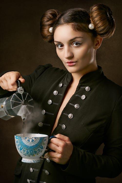 Woman in Black Coat Holding Ceramic Mug