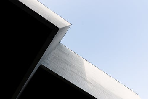 Low Angle Photo of White Concrete Building Under Blue Sky
