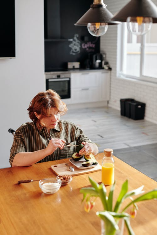 Woman in Black and White Stripe Shirt Sitting by the Table