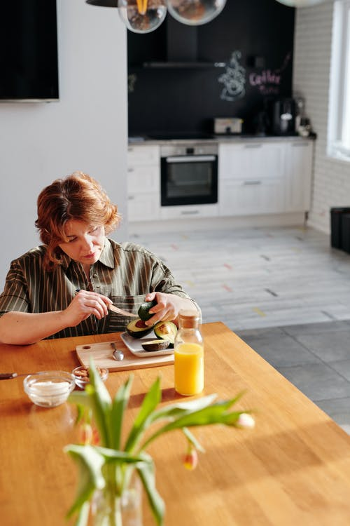 Woman in Brown and White Stripe Shirt Sitting by the Table