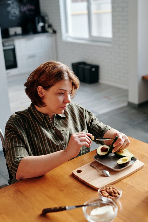 Photo of Woman Slicing an Avocado