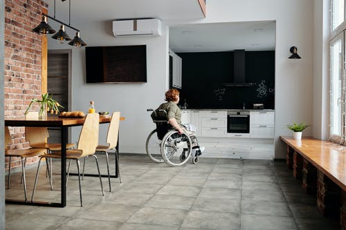 Photo of Woman on Wheelchair Going to the Kitchen