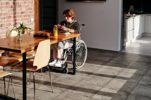 Woman Sitting on Wheelchair by the Wooden Table