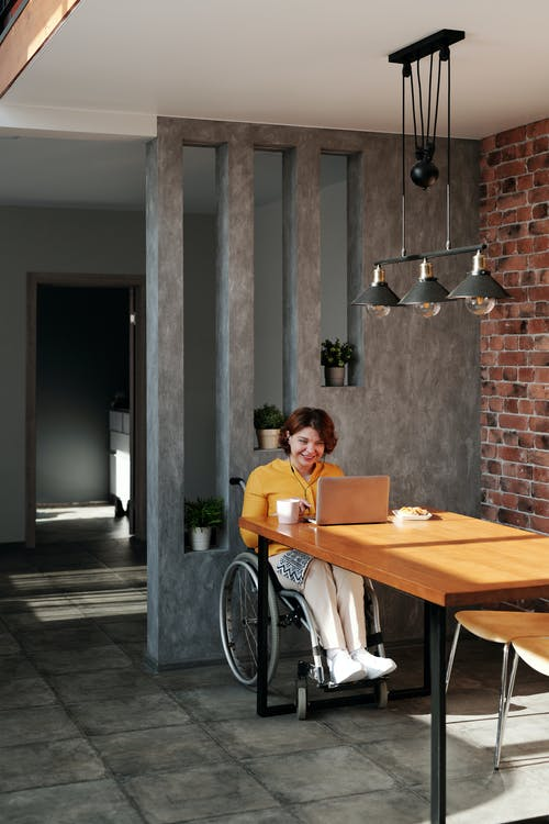 Woman Sitting on Wheelchair While Using Laptop