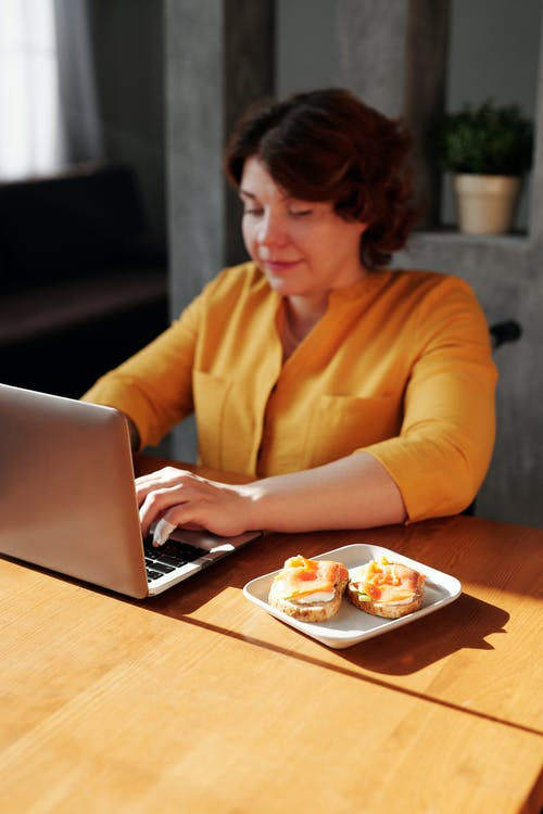 Woman in Orange Long Sleeve Shirt Using Macbook Pro