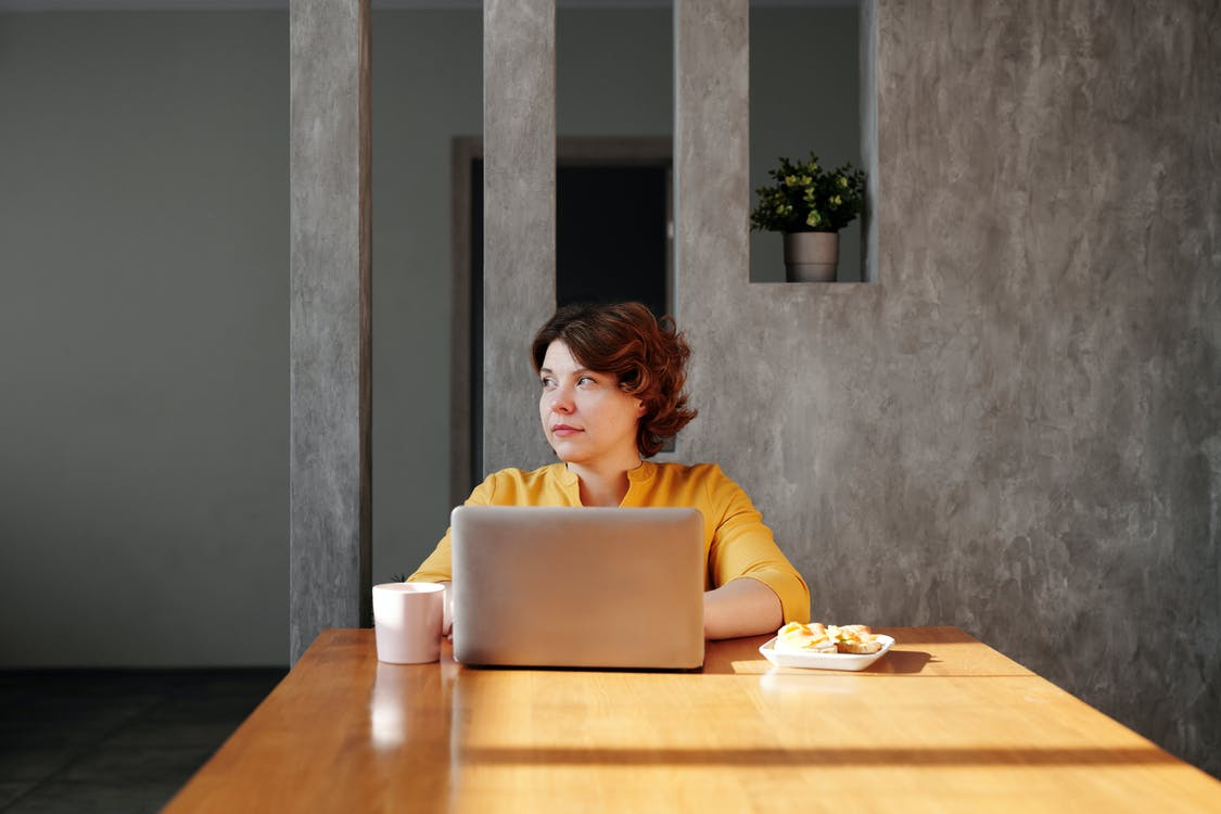 Photo of Woman Sitting by the Table While Looking Away