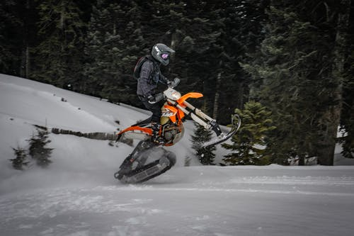 Unrecognizable person performing trick on snowmobile