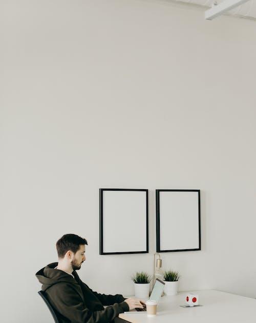 Man in Black Jacket Sitting Beside Green Plant