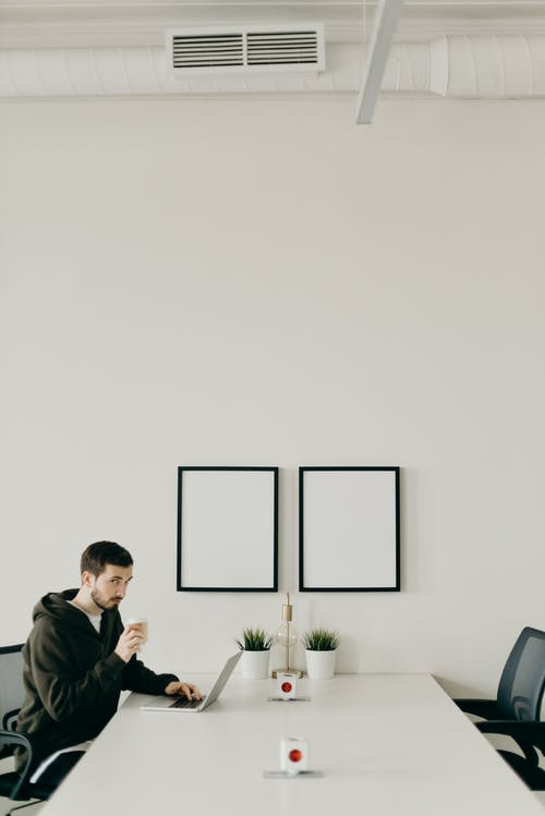 Man In Black Hoodie Using Laptop While Drinking Coffee