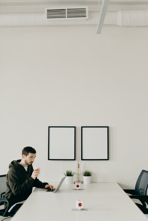 Man In Black Hoodie Using Laptop While Drinking Coffee