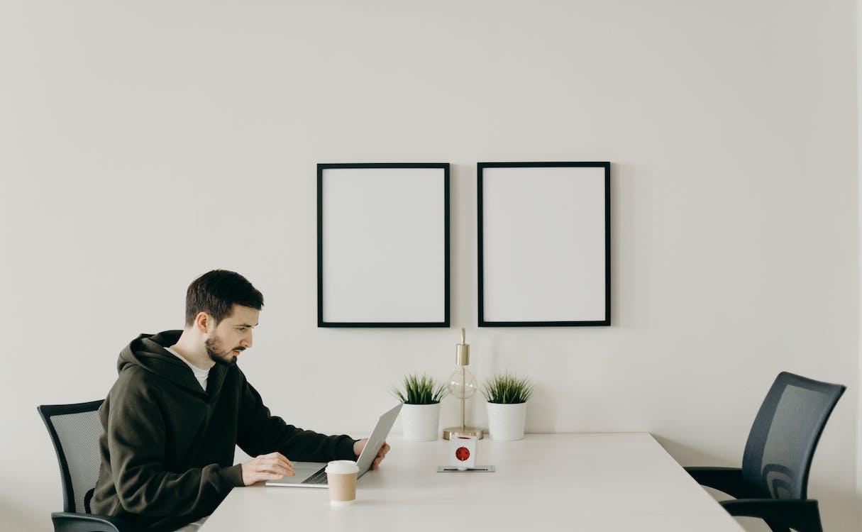 Man in Black Long Sleeve Shirt Sitting at Table