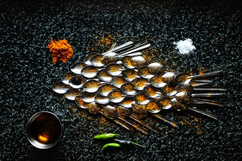 Steel spoons and spices in creative serving