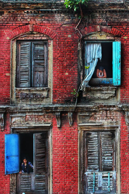 Unrecognizable local people looking out windows in weathered brick house with shabby facade and wooden shutters