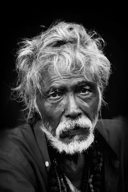 Pensive elderly ethnic man with white beard looking at camera