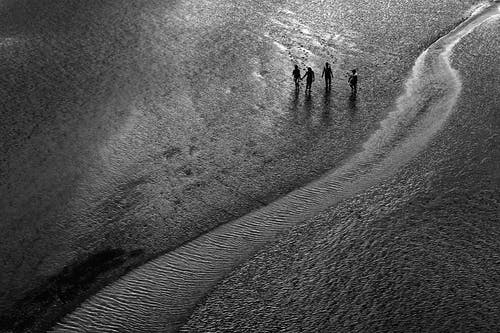 Grayscale Photo of People Walking on Sand