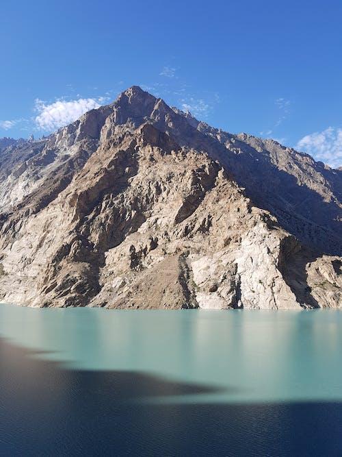 Brown Rocky Mountain Beside Lake