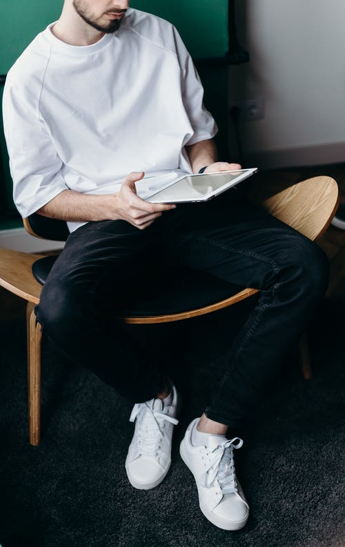 Man in White Shirt and Black Pants Sitting on Brown Wooden Chair