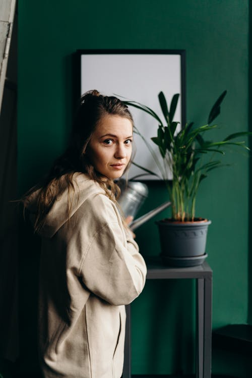 Woman in Beige Coat Sitting Beside Green Potted Plant