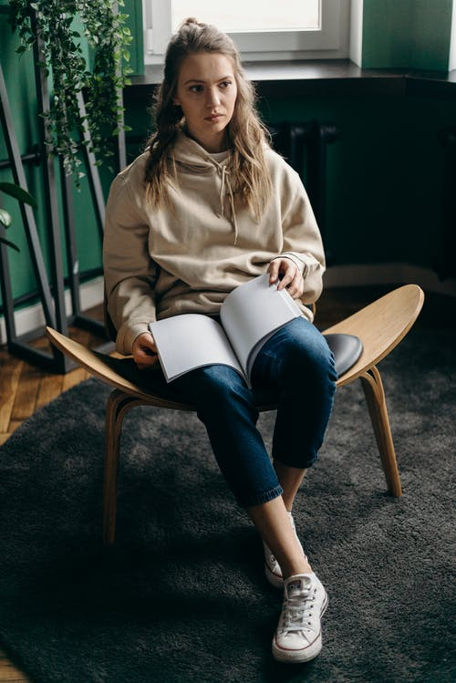 Woman in Brown Jacket and Blue Denim Jeans Sitting on Brown Wooden Chair Reading Book