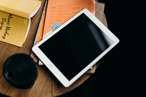 White Ipad on Brown Wooden Table