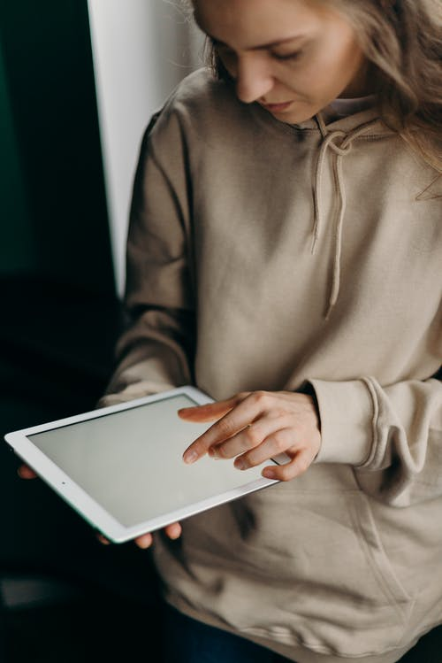 Woman in Gray Long Sleeve Shirt Holding White Tablet Computer