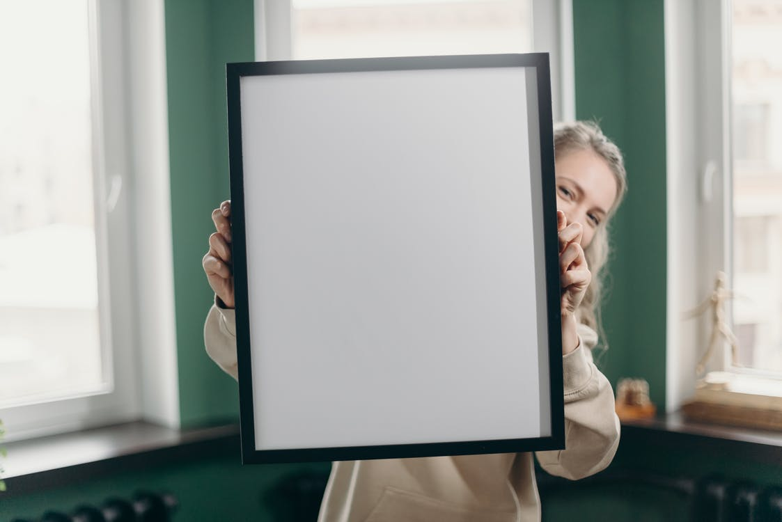 Woman Holding White and Black Frame
