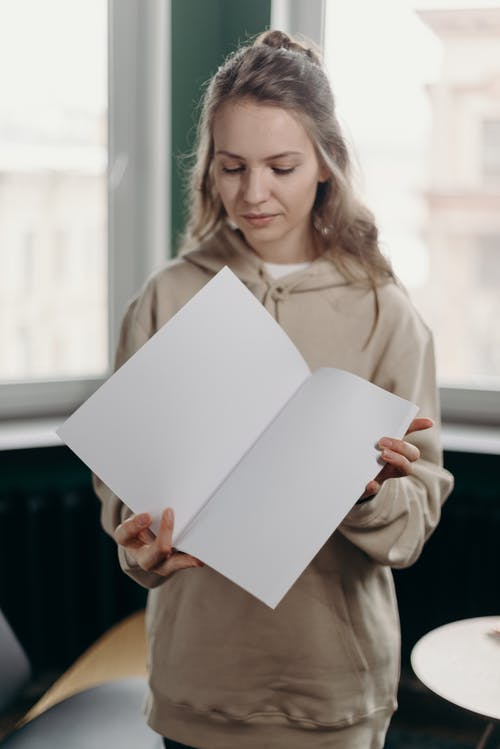 Woman in Brown Coat Holding White Paper