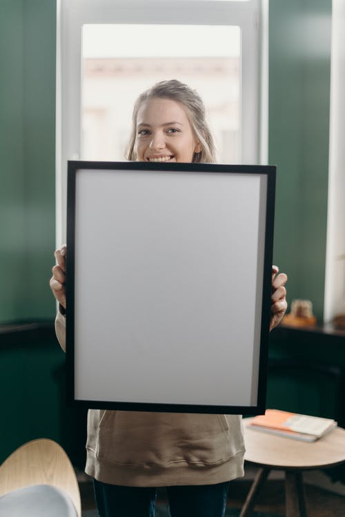 Woman Holding Black Frame With White Screen