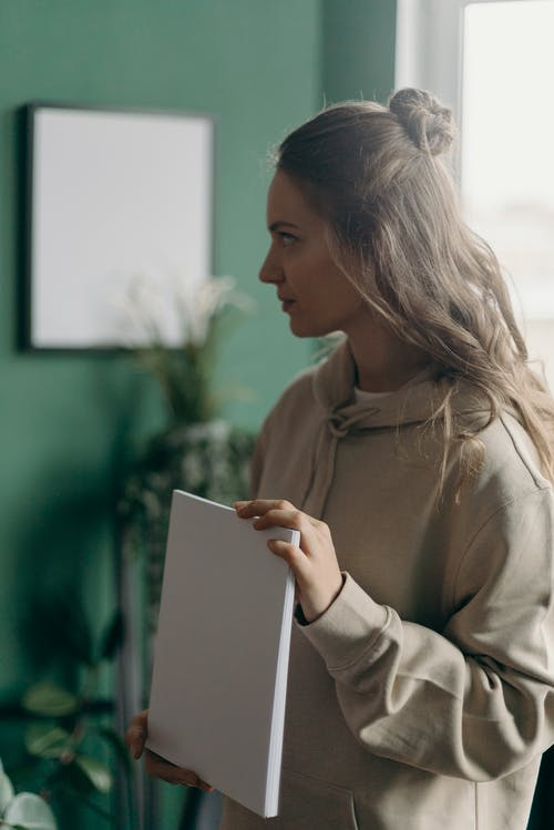 Woman in Brown Long Sleeve Shirt Holding White Book