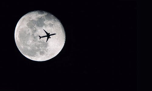Silhouette of Airplane in front of Full Moon
