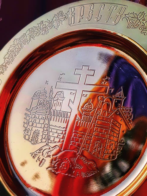 Decorative shiny golden plate with carved orthodox cross and churches and ornamental details