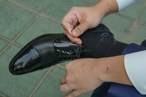 Person Tying Black Leather Shoe